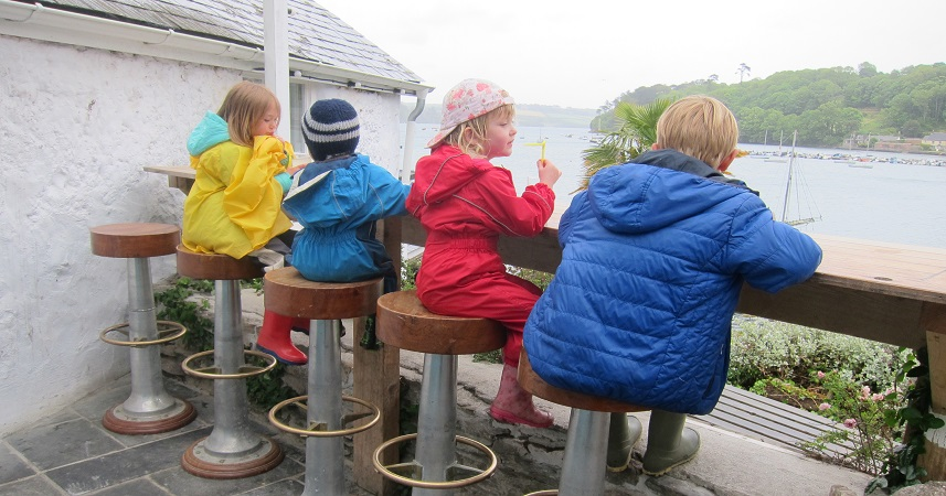 Children in waterproof clothing sitting on stools outdoors