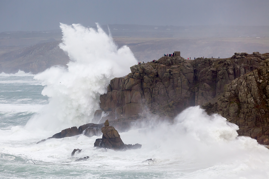 Huge waves crashing into cliffs at Sennen Cove photographed from Lands End Cornwall England UK