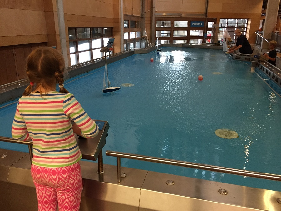 Girl trying out remote control boat at the National Maritime Museum