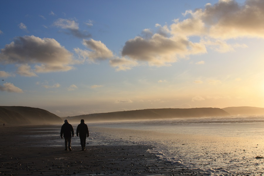 Couple enjoying a winter walk on the beach in Cornwall