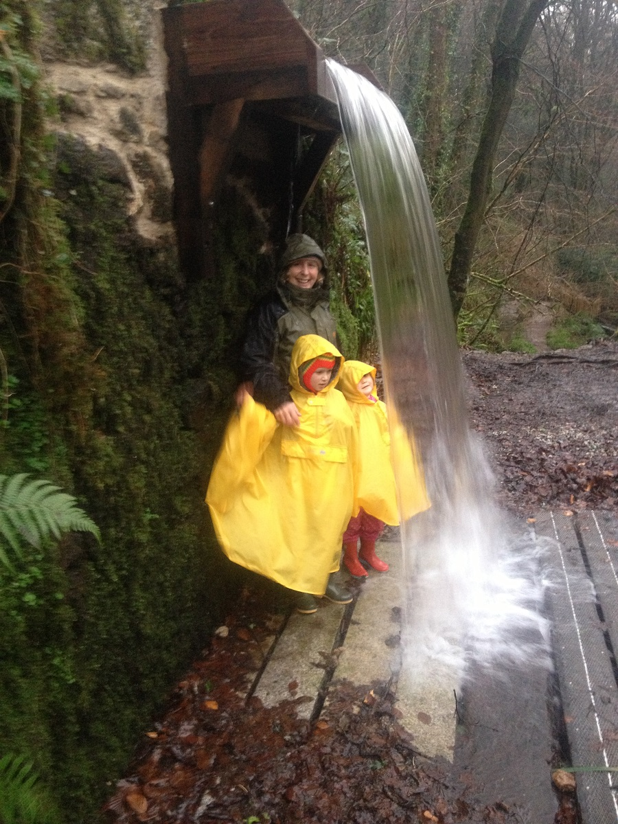 Nanny Pat and grandchildren under a waterfall at Kennall Vale